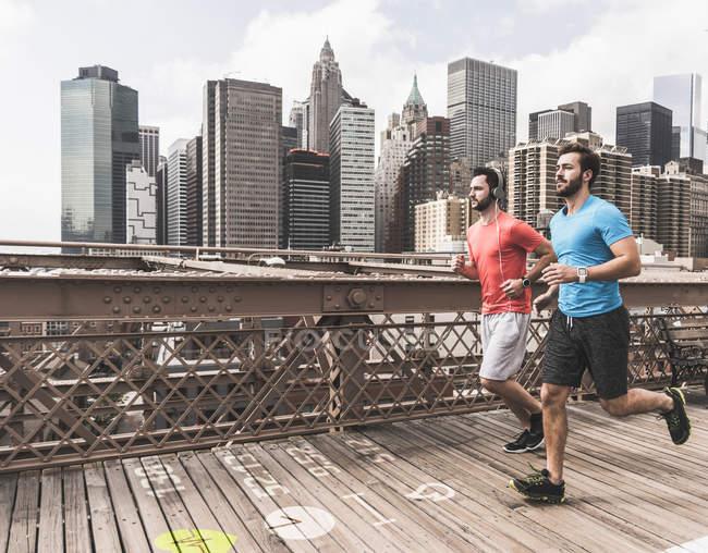 США, Нью-Йорк, двое мужчин, бегущих по Бруклинскому мосту с данными по земле — стоковое фото