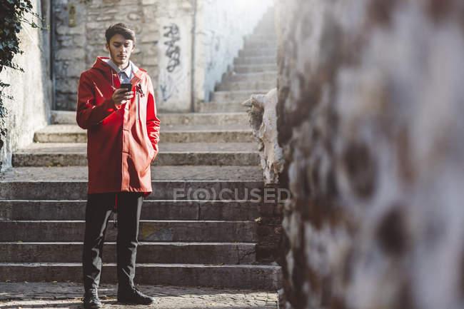 Italia, Verona, turista usando teléfono inteligente en las escaleras - foto de stock