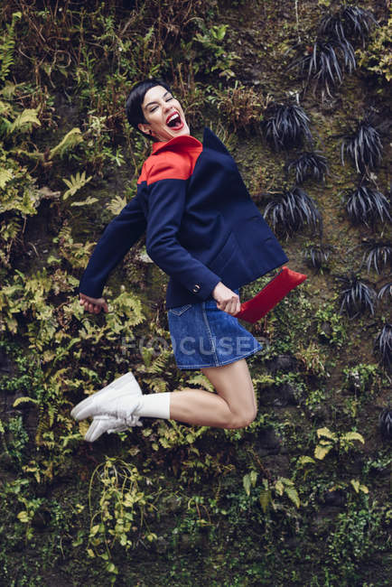 Портрет модною молодої жінки, що стрибає в повітрі перед живою стіною — стокове фото