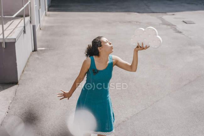 Mulher de pé no quintal, segurando símbolo nuvem, soprando beijo — Fotografia de Stock