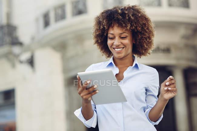 Mulher sorridente com penteado afro usando tablet na cidade — Fotografia de Stock