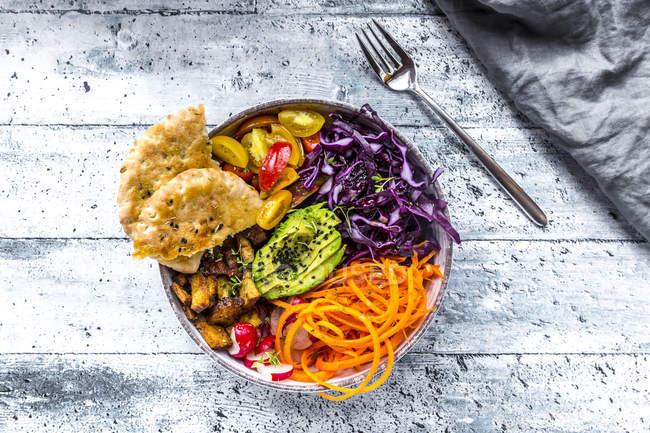 Veggie-Schüssel mit Tomaten, Tofu, Rotkohl, Avocado, Karotten, rot rötlich, Kresse, schwarzer Sesam und Pita-Brot — Stockfoto