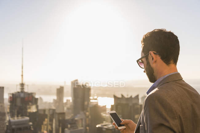 USA, New York City, businessman with cell phone on Rockefeller Center observation deck — Stock Photo