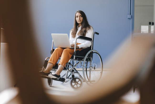 Jeune femme handicapée assise en fauteuil roulant, en utilisant un ordinateur portable — Photo de stock