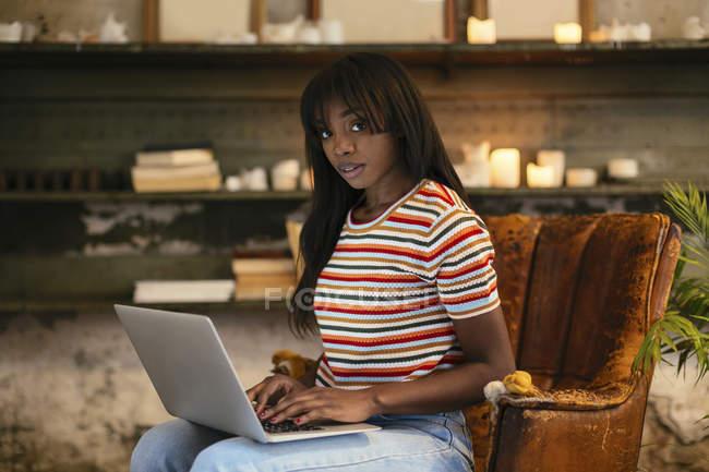 Ritratto di giovane donna seduta su una vecchia sedia di pelle che lavora su un computer portatile in un loft — Foto stock