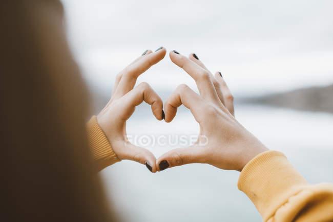 Menina fazendo uma forma de coração com os dedos — Fotografia de Stock