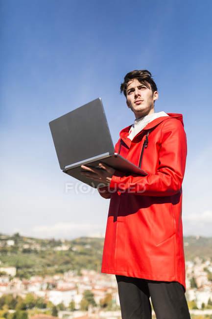 Італія, Верона, молода людина, що використовує ноутбук проти синього неба — стокове фото