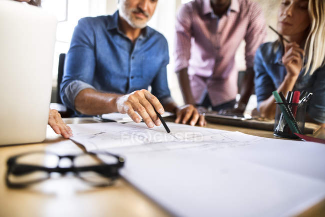 Colleagues discussing blueprint at desk in office — Stock Photo