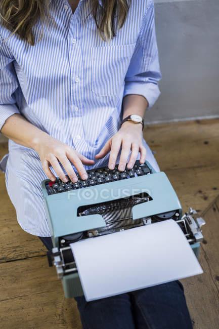 Primer plano de la mujer sentada en el suelo y utilizando la máquina de escribir - foto de stock