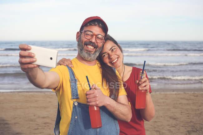 Пара з безалкогольними напоями, що приймає селфі з смартфоном на пляжі — стокове фото