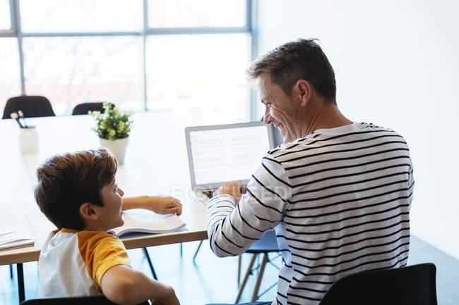 Sorrindo pai e filho sentado à mesa e usando laptop — Fotografia de Stock