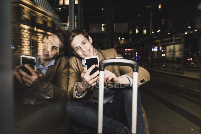 Smiling businessman using cell phone at tram station at night — Stock Photo