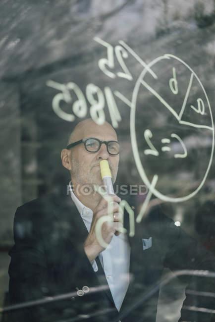 Старший бизнесмен мозгового штурма, рисунок формулы на оконном стекле — стоковое фото