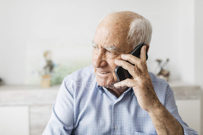 Happy senior man using smartphone at home — Stock Photo