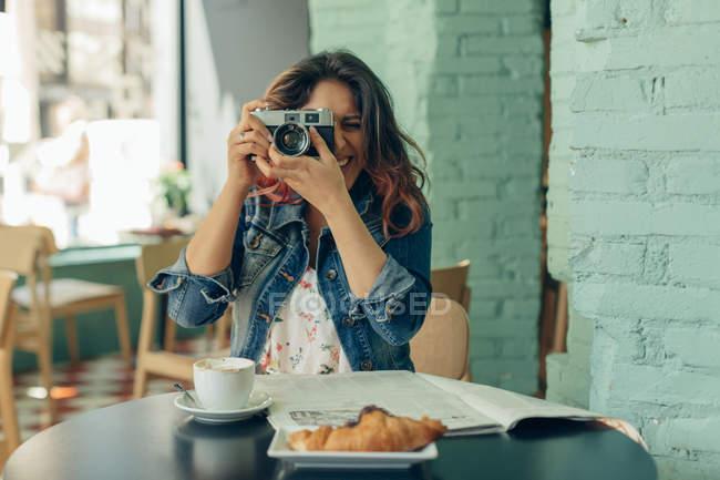 Rindo mulher sentada no café tirando fotos com câmera — Fotografia de Stock