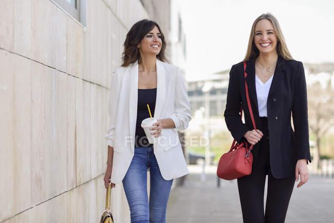 Портрет двух счастливых бизнесвумен с сумочками и кофе идти пешком по тротуару — стоковое фото