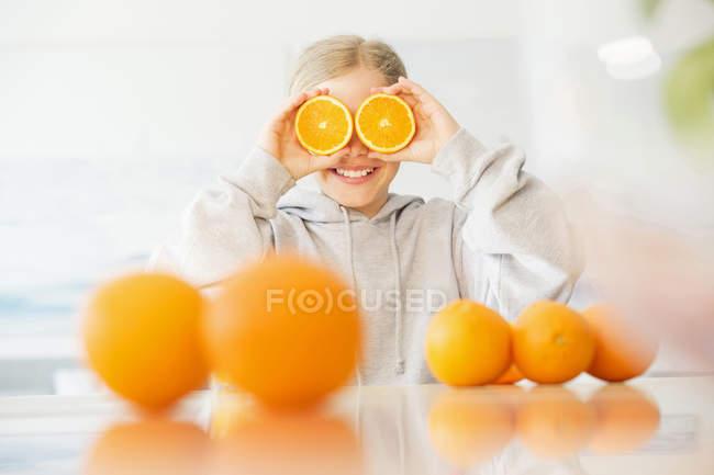 Riendo chica cubriendo sus ojos con mitades de naranja - foto de stock