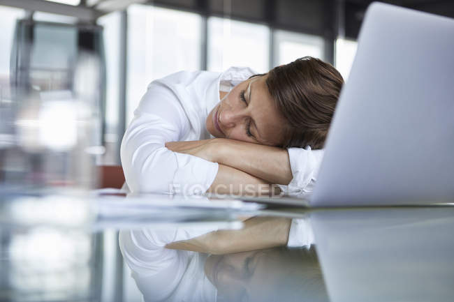 Businesswoman with closed eyes lying on glass table in office in front of laptop — стокове фото
