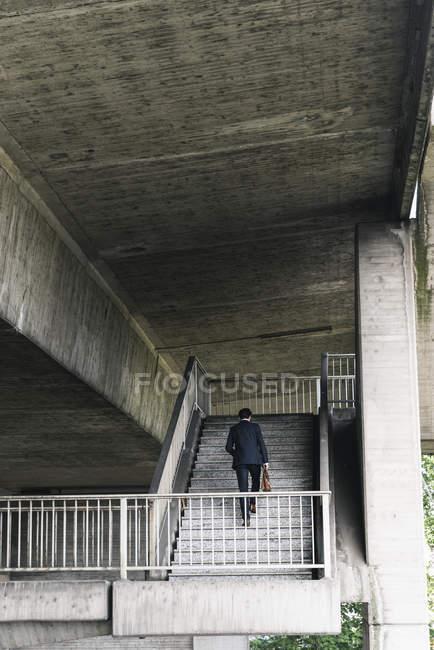 Homme d'affaires au passage inférieur marchant à l'étage — Photo de stock