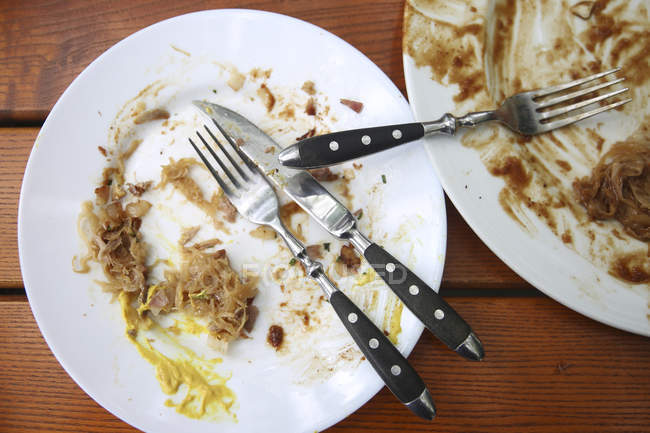 Essensreste mit Besteck auf Holztisch — Stockfoto