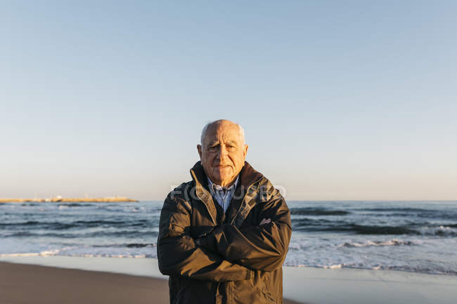 Senior man standing on beach — Stock Photo