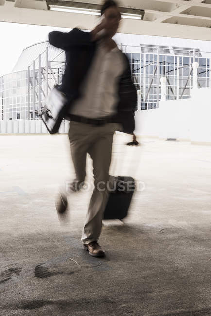 Businessman with rolling suitcase in a hurry at parking garage — Stock Photo