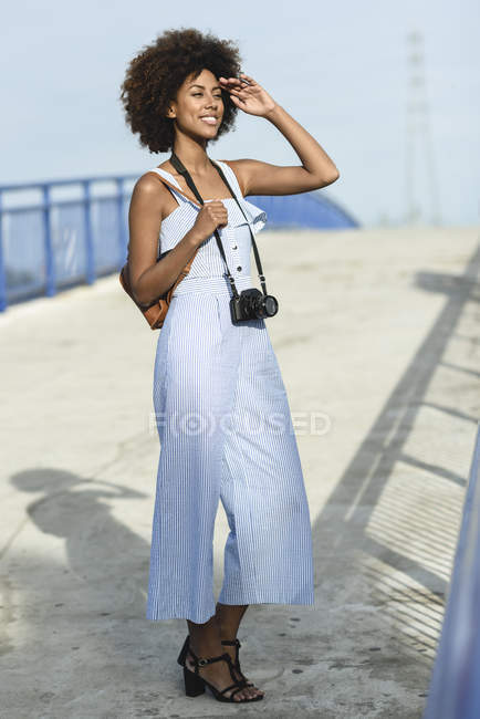 Portrait of fashionable young woman with camera and backpack — Stock Photo