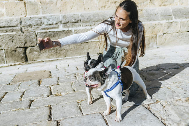 Young woman using smartphone, taking a selfie with her dogs — Stock Photo