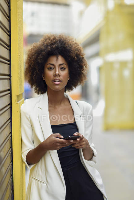 Portrait of fashionable young woman with curly brown hair — Stock Photo