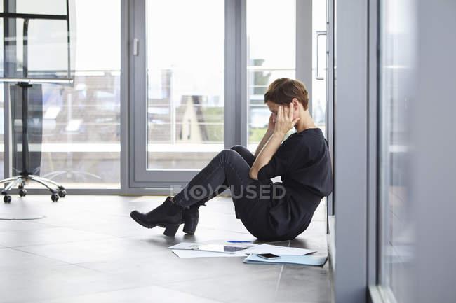 Empresária sobrecarregada sentada no chão no escritório — Fotografia de Stock