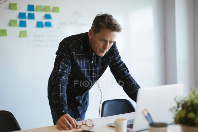 Businessman standing at desk in office looking at laptop — Stock Photo