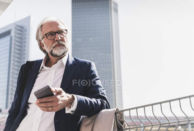 Serious mature businessman in the city looking around — Stock Photo
