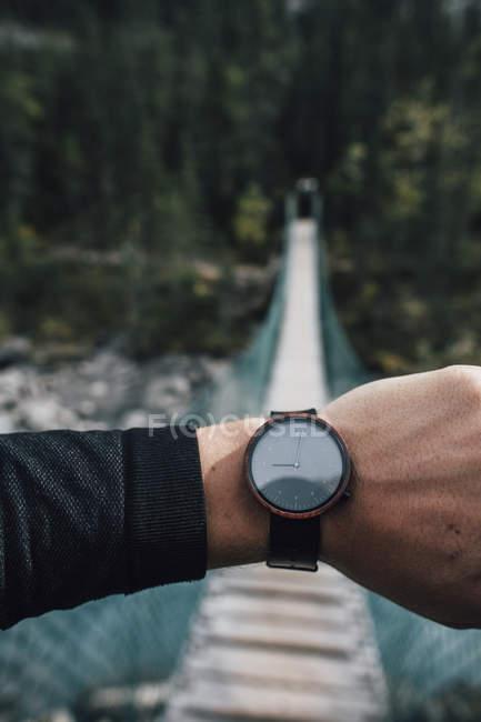 Мужская рука с часами перед раскачивающимся мостом — стоковое фото