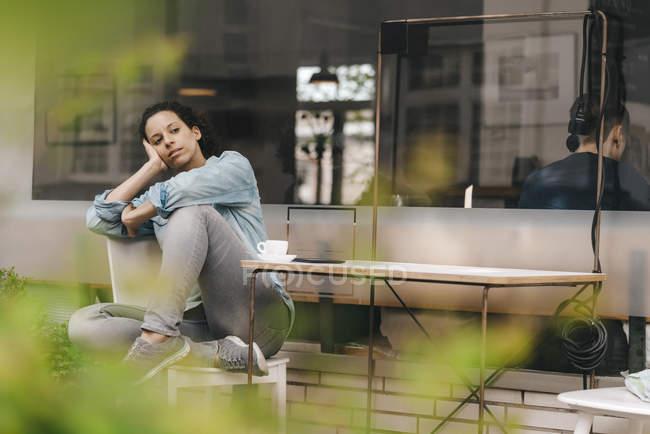 Уставшая женщина отдыхает перед кофейней — стоковое фото