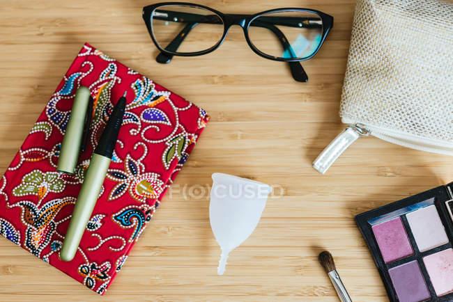 Menstruationstasse auf Tisch und Notizbuch, Stift und Brille — Stockfoto