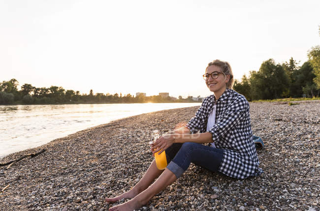 Femme blonde assise au bord de la rivière le soir — Photo de stock