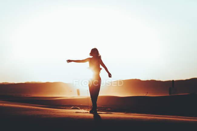 Silhouette einer Frau, die bei Sonnenuntergang in Wüstenlandschaft steht — Stockfoto