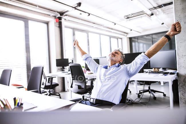 Felice uomo d'affari maturo seduto alla scrivania in ufficio con le braccia alzate — Foto stock