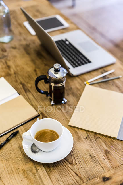 Laptop and coffee on wooden table at home — Stock Photo