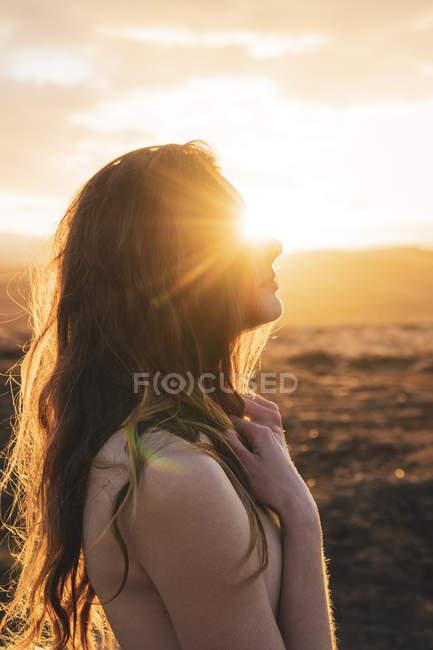 Islândia, jovem mulher nua ao pôr do sol — Fotografia de Stock