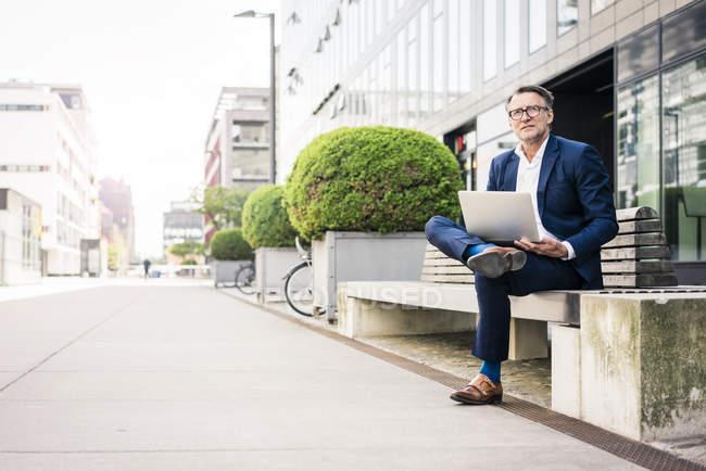 Зрелый бизнесмен с помощью ноутбука на скамейке на открытом воздухе — стоковое фото