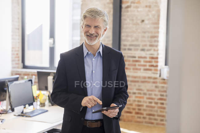 Mature man standing in his office, using didgital tablet — Stock Photo