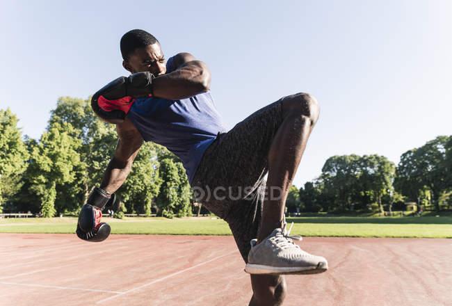 Молоді афро-американського людина навчання боксу на спортивному полі, на відкритому повітрі — стокове фото