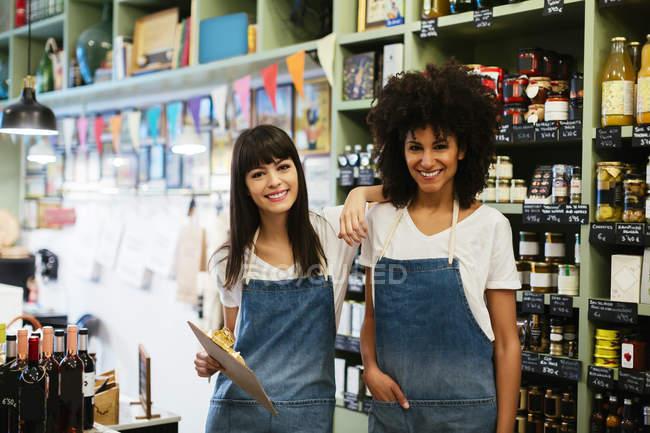 Portrait de deux travailleuses souriantes posant en magasin — Photo de stock