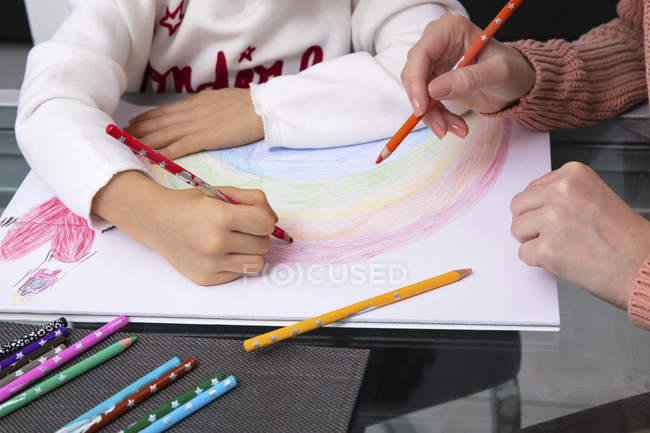 Mother and little daughter drawing a rainbow, partial view — Stock Photo