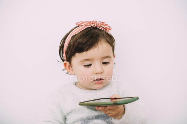 Portrait of baby girl looking at cell phone — Stock Photo