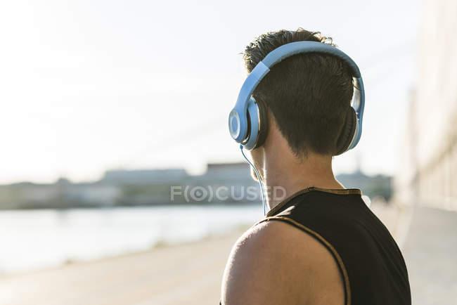 Joven con auriculares mirando a la distancia - foto de stock