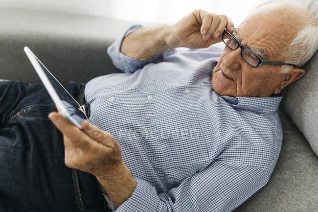 Hombre mayor navegando por Internet en una tableta mientras está acostado en el sofá - foto de stock