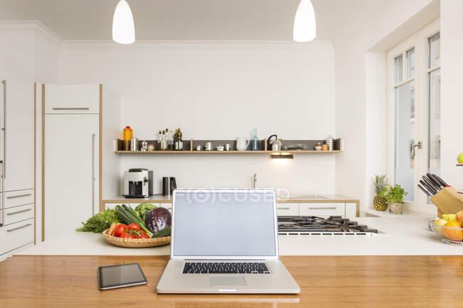 Ноутбук і планшет на кухні. — стокове фото