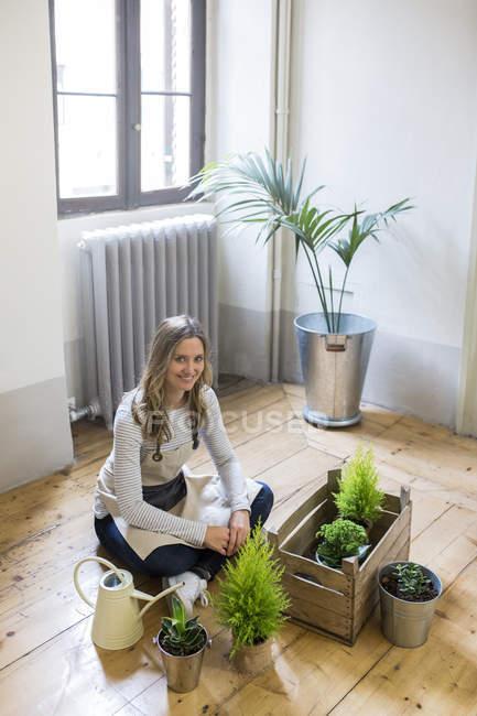Porträt einer lächelnden Frau, die zu Hause auf dem Boden sitzt und sich um Pflanzen kümmert — Stockfoto